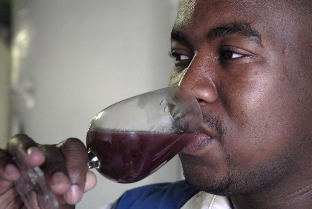 Junior winemaker Philani Gumede tests a new batch of wine at the Orange River Wine Cellars