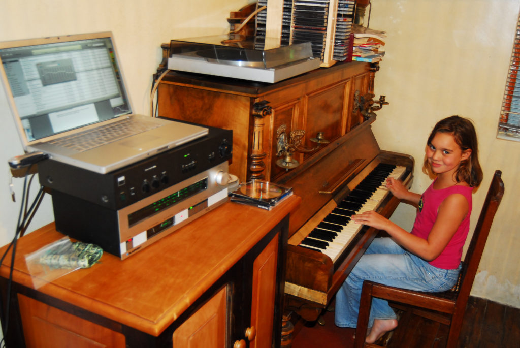 Eight-year-old Naomi Scheepers plays the piano while listening to music on the computer in her family home