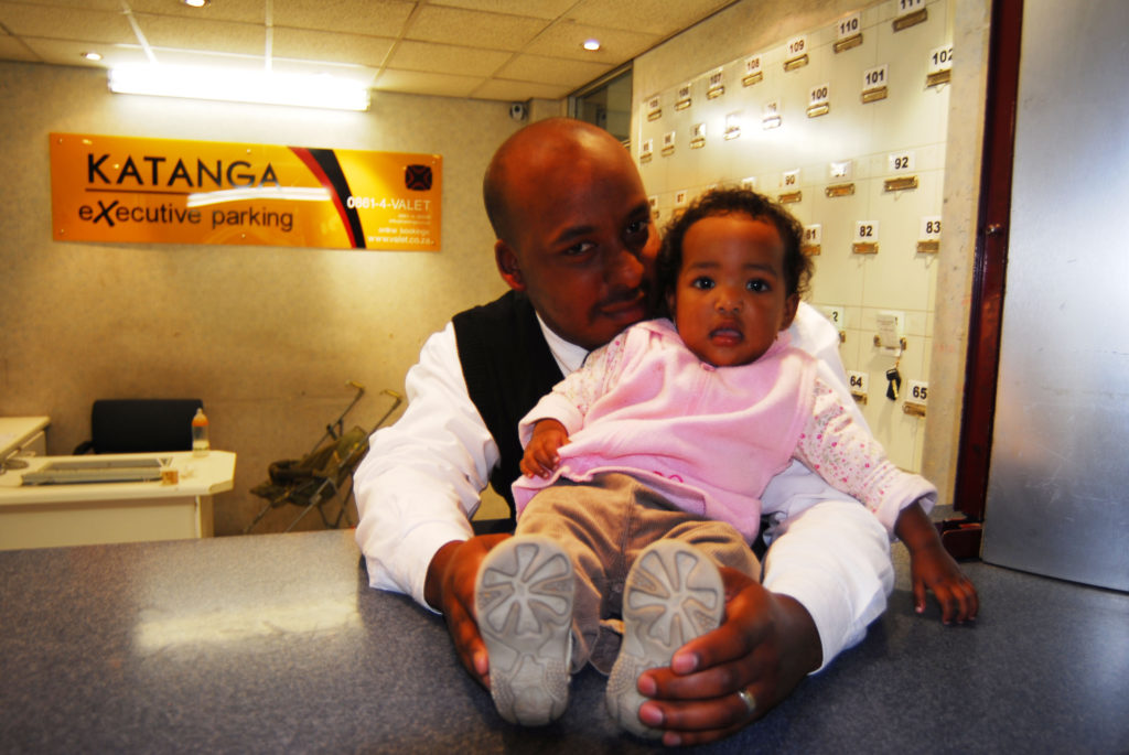 Mustapha Mahwayo (35), with his one-year-old daughter Maahirahl, at his job in Cape Town Airport