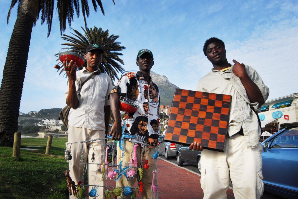 Samuel Kalule, Peter Kanyerere, and an unnamed friend sell their crafts at Camps Bay Beach