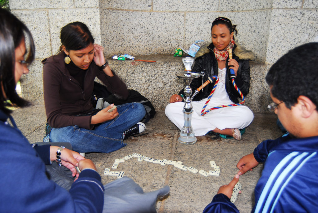 University of Cape Town students Farah Noordien, Mishkah Abrahams, Ayesha Molangee and Kyle Williams play dominoes and smoke a traditional hookah at the Rhodes Memorial while they wait for their next exam