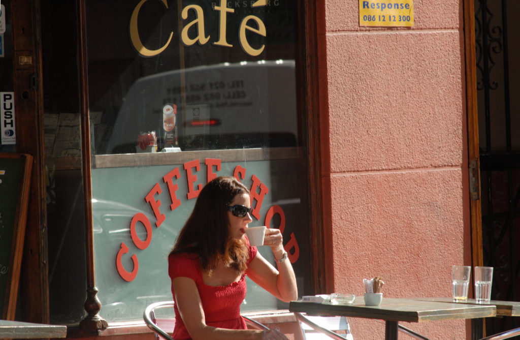 A woman enjoys a cup of coffee at a cafe in the city centre