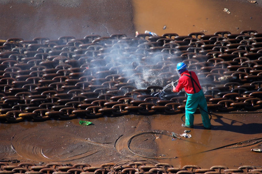 Cape Town, Western Cape province: A harbour worker cleans chains used to keep oil rigs in place