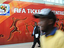 A Ghanaian journalist walks past the Fifa Ticketing Centre in Maponya Mall, Soweto