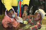 5. A member of the Brand SA staff wipes the children's hands before lunch.