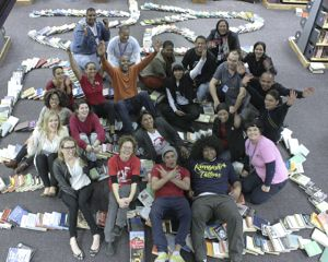 The Open Book and Central Library team celebrate among fallen books after a successful domino run of 2 528 books, hopefully setting a new record. Photo: Steve Kretzmann/WCN