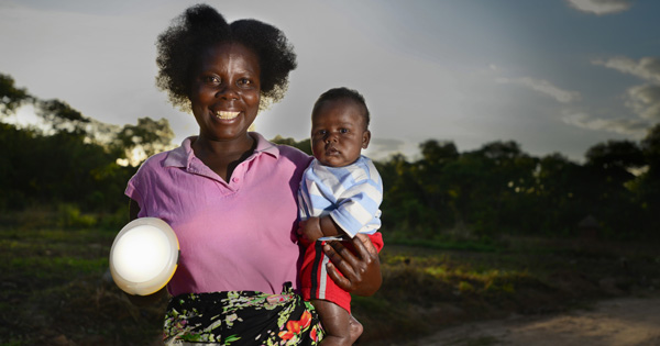 Priscilla and her son in Zambia with a solar light. These lights are bringing clean, safe, affordable lighting to homes for the first time.