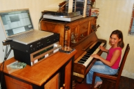 Eight-year-old Naomi Scheepers plays the piano while listening to music on the computer in her family home in Cape Town, Western Cape.