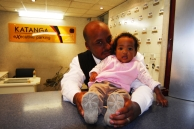 Mustapha Mahwayo (35), with his one-year-old daughter Maahirahl, at his job in Cape Town Airport, where he parks cars for Executive Parking. Cape Town, Western Cape.