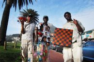 Cape Town, Western Cape province: Samuel Kalule, Peter Kanyerere, and an unnamed friend sell their crafts at Camps Bay Beach