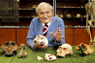 Emeritus Professor Phillip V Tobias, an acclaimed South African anthropologist, with a collection of fossil hominid skulls from east and southern Africa at the Fossil Laboratory of the University of the Witwatersrand. The skull and jawbone of the Taung Child, a famous specimen of Australopithecus africanus, are directly in front of him.